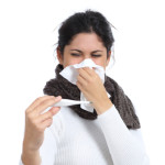 Ill woman with a handkerchief in the nose looking thermometer